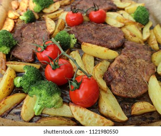 Roasted pork steaks with potatoes, cherry tomatoes and broccoli with olive oil and rosemary. Healthy delicious food. Grilled food, summer outdoor eating. Top view.