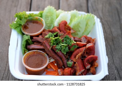 Roasted pork and Stuffed roast pork Placed on a foam tray with sauce. The background is wooden, Street food Thailand.