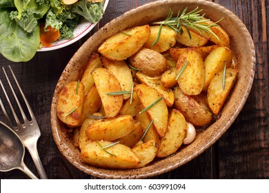 Roasted potato in brown bowl with fresh salad on wooden table