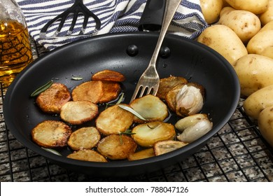 roasted potato slices made from raw potato with garlic and olive oil in a pan