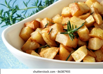 Roasted potatoes with fresh rosemary, in white serving bowl.