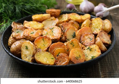 Roasted potatoes in a frying pan on wooden table, close up
