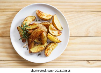 roasted potatoes  with rosemary and garlic in white plate on wooden background