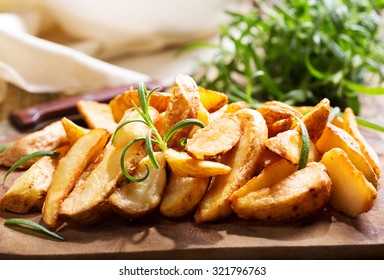 roasted potatoes with rosemary on wooden table