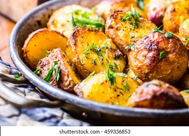 Roasted potatoes with smoked bacon garlic salt pepper cumin dill and herb decoration.