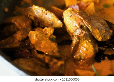 Roasted poultry liver with apple in curry sauce, closeup.