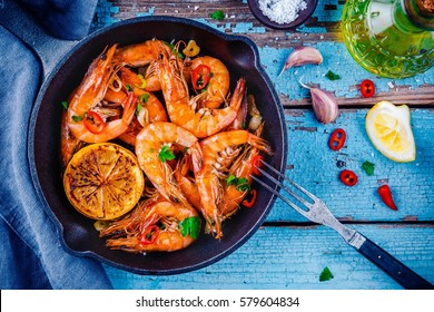 Roasted prawns with parsley, chili pepper, garlic and lemon in frying pan on rustic background