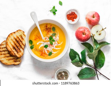 Roasted pumpkin and apples vegetarian soup on light background, top view. Flat lay. Healthy vegetarian food concept