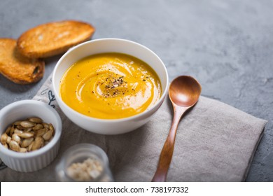 Roasted pumpkin and carrot soup with black pepper and pumpkin seeds on grey concrete background.