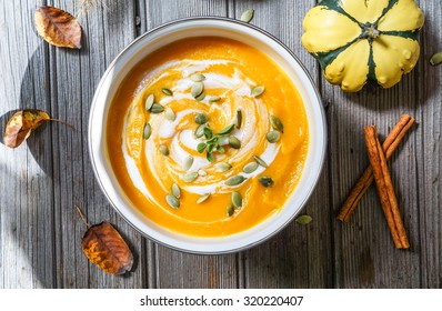 Roasted pumpkin and carrot soup with cream and pumpkin seeds on white wooden background