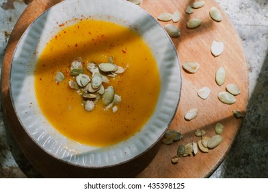 Roasted pumpkin and carrot vegan soup with coconut milk and pumpkin seeds on wooden background. Copy space. Homemade