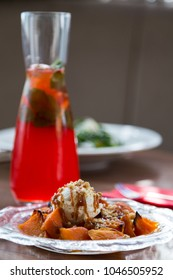 Roasted pumpkin dessert with walnuts, ice cream and caramel sauce served with strawberry lemonade