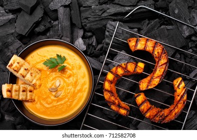 Roasted pumpkin on a grid on charcoal background.BBQ pumpkin.Top view