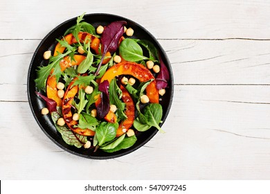 .Roasted pumpkin salad with chick pea and fresh herbs overhead a white wooden background.