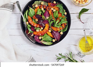 Roasted pumpkin salad with chick pea and fresh herbs overhead a white wooden background. Overhead view