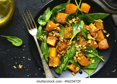 Roasted pumpkin salad with spinach and walnut on a black plate on a stone background.Top view.