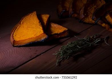 Roasted pumpkin slices on wooden background