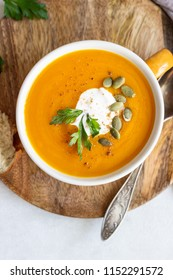 Roasted pumpkin soup with cream, parsley and pumpkin seeds on light background.
