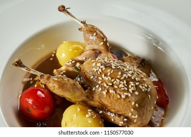 Roasted quail with vegetables potatoes tomatoes on white plate close up