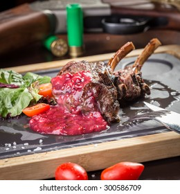 Roasted rack of deer with berry sauce on wooden table