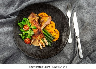 Roasted rack of lamb served with asparagus, yellow tomatoes and lamb sauce. Loin lamb Served in black stone plate with fork and knife. Gray background. Tuna salad. Top view from above horizontal.