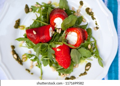 Roasted red peppers stuffed with cheese with arugula and basil pesto