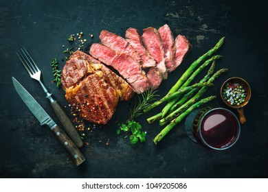 Roasted rib eye steak with green asparagus and wine on dark background