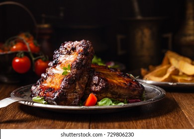 Roasted ribs, served on an old plate. Front view. Dark or balck background.