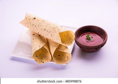 Roasted roll papad is an Indian traditional started food or side dish, served with tomato ketchup over white background. Selective focus