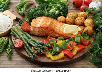roasted salmon with asparagus and vegetables in metal pan on rustic background