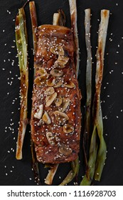 Roasted salmon fillet on bed of spring onions, glazed with balsamic vinegar, garlic and sesame seeds. Black wooden background, top view shot.