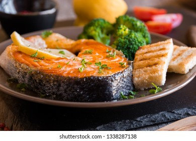 Roasted salmon fish steak with croutons and broccoli on dark background