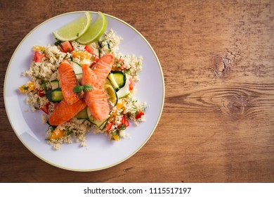 Roasted salmon fish with tomato couscous, zucchini and lime on white plate. overhead, horizontal, room for text