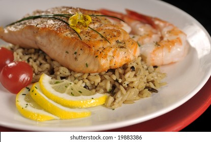 Roasted salmon served with shrimps, cherry tomatoes, basmati spiced rice and lemon.