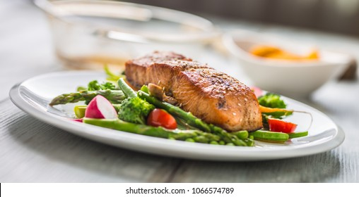 Roasted salmon steak with asparagos broccoli carrot tomatoes radish green beans and peas. Fish meal with fresh vegetable.