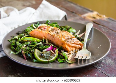 Roasted salmon steak with fresh salad from chard leaves, red onion and lime on a plate on a wooden table, selective focus