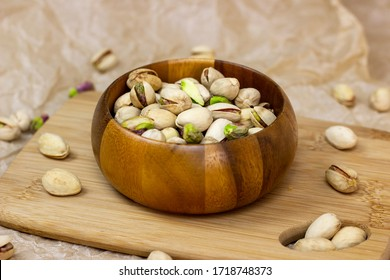 Roasted salted pistachio nuts in nutshell in wooden bowl on textured background
