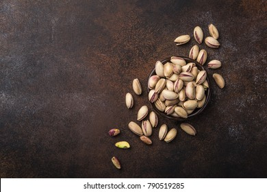 roasted and salted pistachios on brown bacckground. Top view.