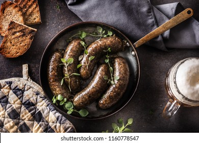 Roasted sausages in pan with bread herbs and draft beer. Traditional european food bratwurst jaternice or jitrnice.