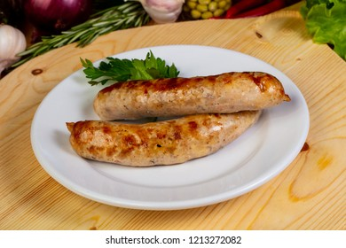 Roasted sausages in the plate served parsley