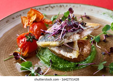 Roasted seabass fillet, served with spinach puree, peas with white onions and baked potatoes.
