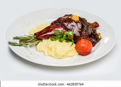 roasted shank of lamb, marinated in red wine with prunes and garlic. with mashed potatoes and baked tomatoes. On a white background and a white plate