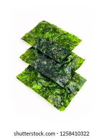 Roasted sheets of seaweed, a pile, isolated on white background. Asian healthy dry nori snack food.