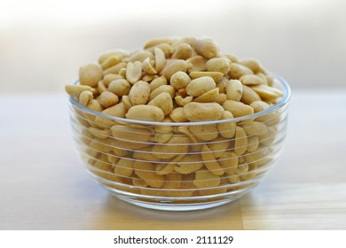 Roasted, shelled, and salted peanuts in a glass bowl on a butcher-block tabletop