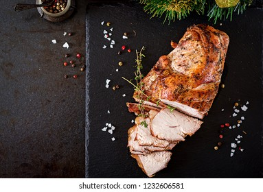 Roasted sliced Christmas ham of turkey on dark rustic background. Top view. Festival food.