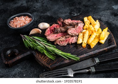 Roasted sliced machete skirt beef meat steak on wooden board with french fries. Black background. Top view.