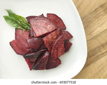 Roasted slices of beetroot. Portion served on a white plate. Wooden background. Top view.