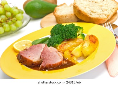 roasted slices of pork with deep fried potatoes and broccoli