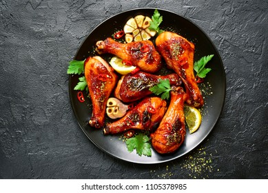 Roasted spicy chicken legs on a plate over black slate,stone or concrete background.Top view with copy space.