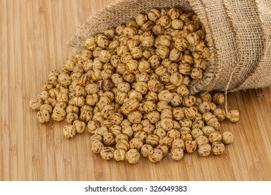 Roasted spicy chickpeas in a straw sack on bamboo backgorund